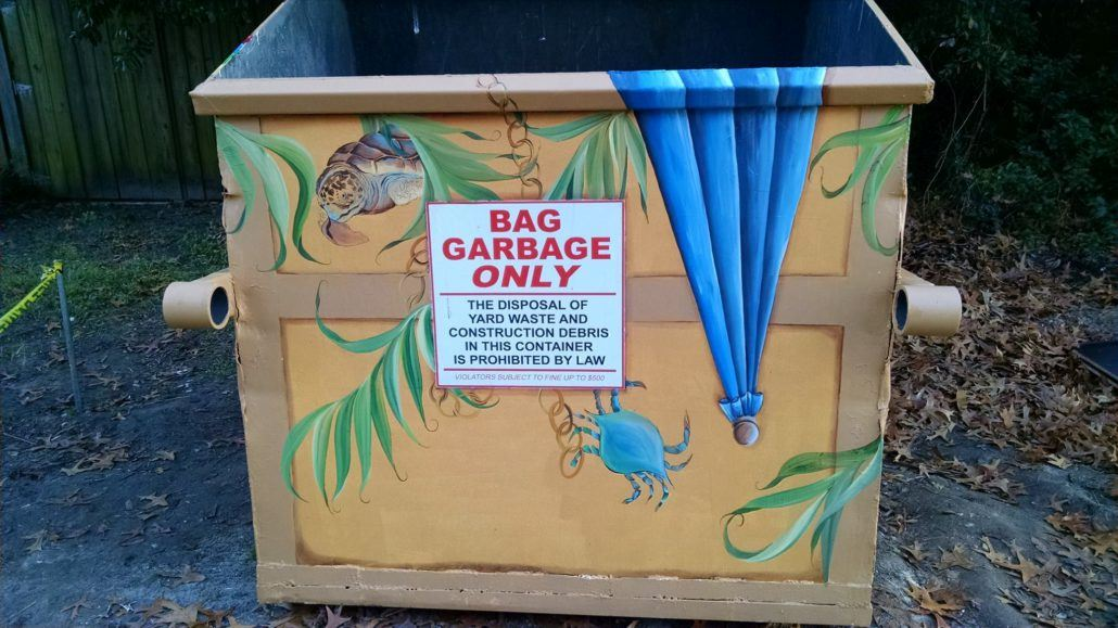 Decorated Dumpster with a Sign Showing Bag Garbage Only