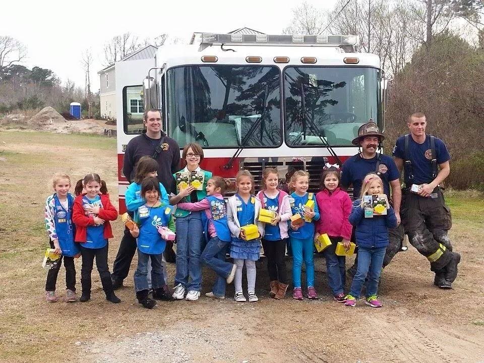 Group of Girl Scouts Standing with Firefighters in Front of a Fire Truck