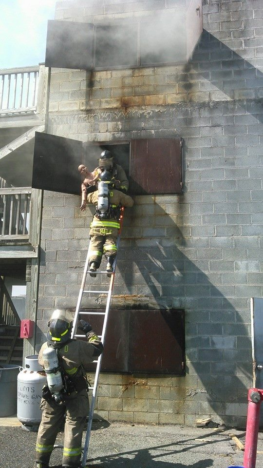Training Exercise on a Ladder while a Firefighter Holds a Dummy