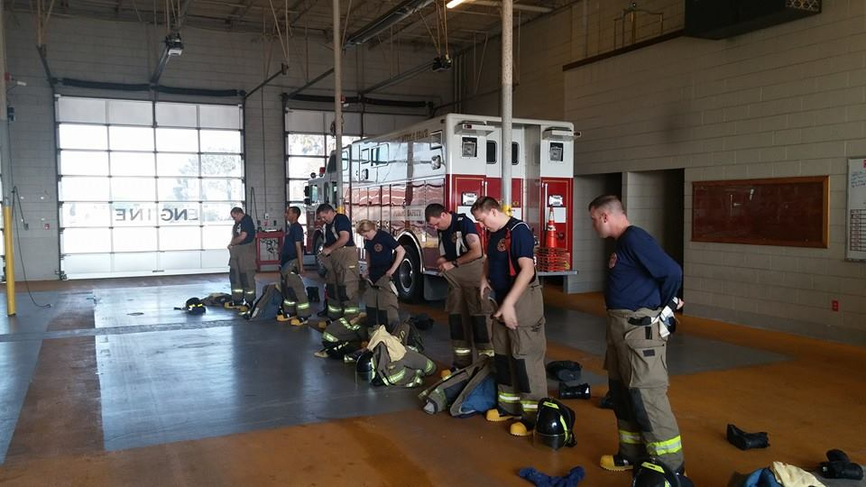 Firefighters Standing in a Formation Putting on Their Gear in a Fire House