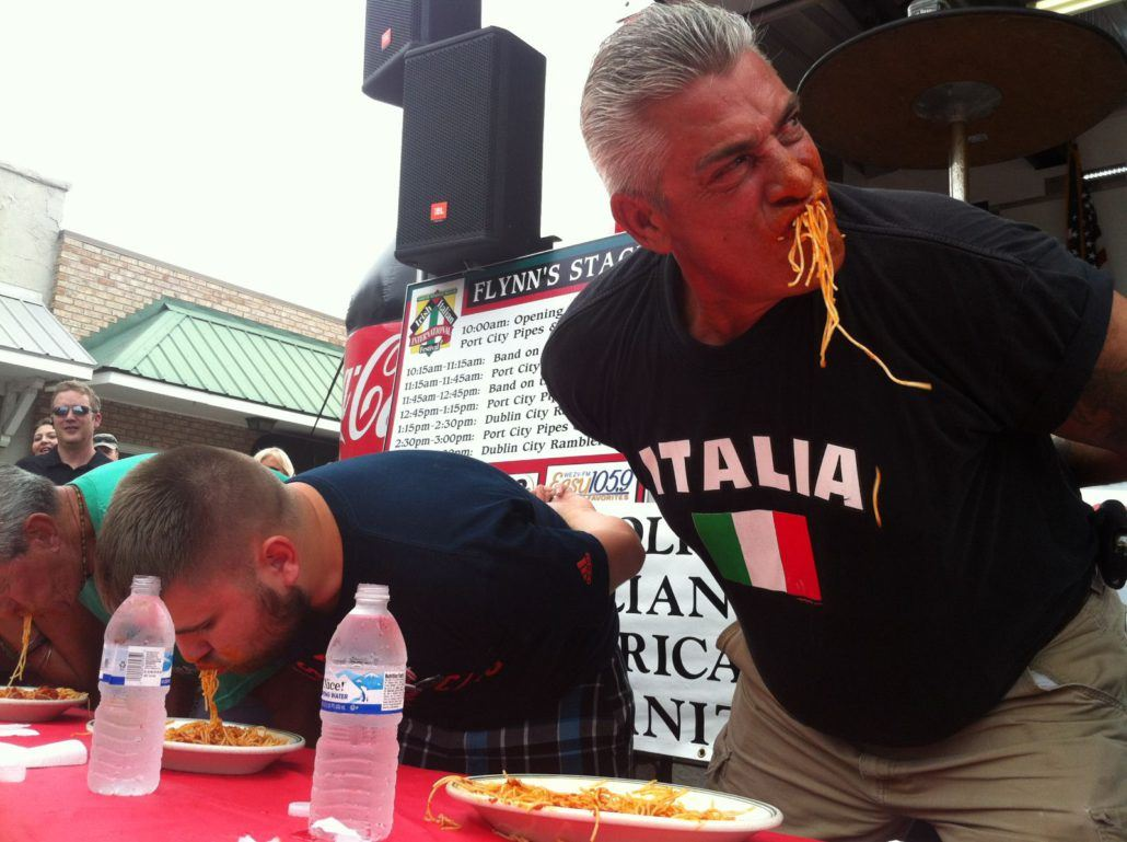 Participants with Their Hands Behind Their Back Eating Plates of Spaghetti