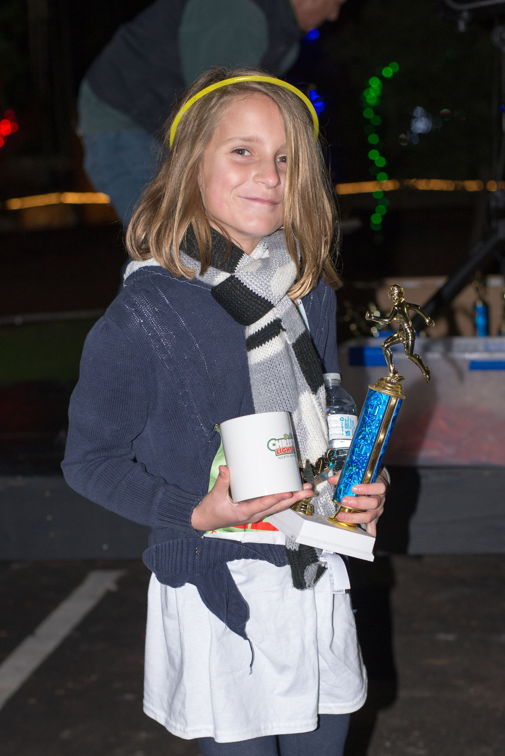 Child Holding a Mug and Trophy with a Glow Headband