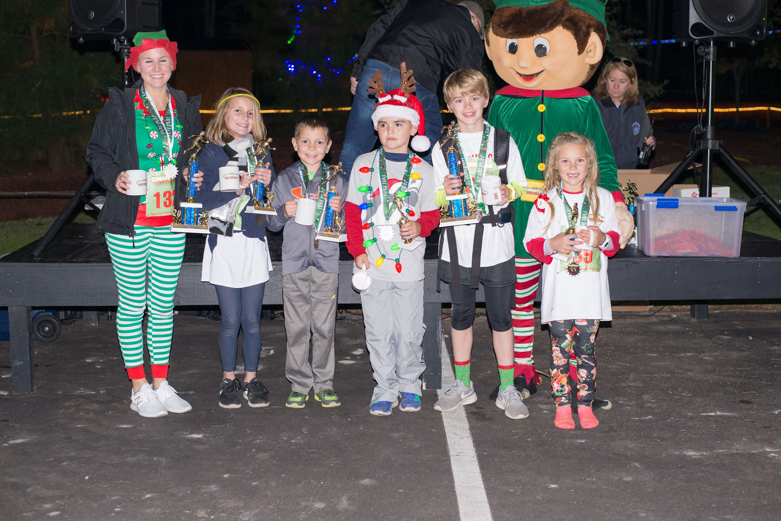 Kids Holding Trophies in Christmas Outfits