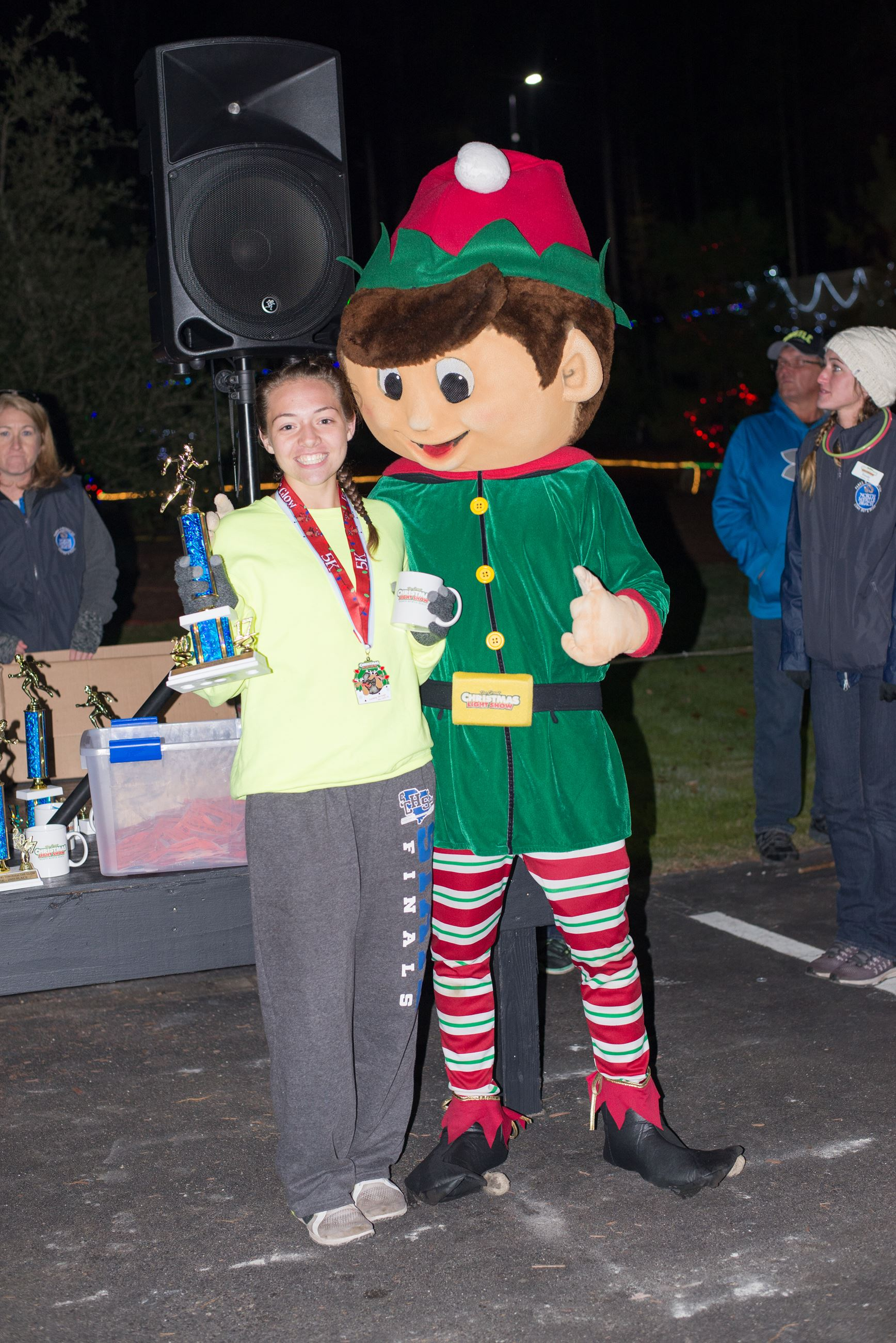 Young Woman Holding a Mug and Trophy Posing with an Elf