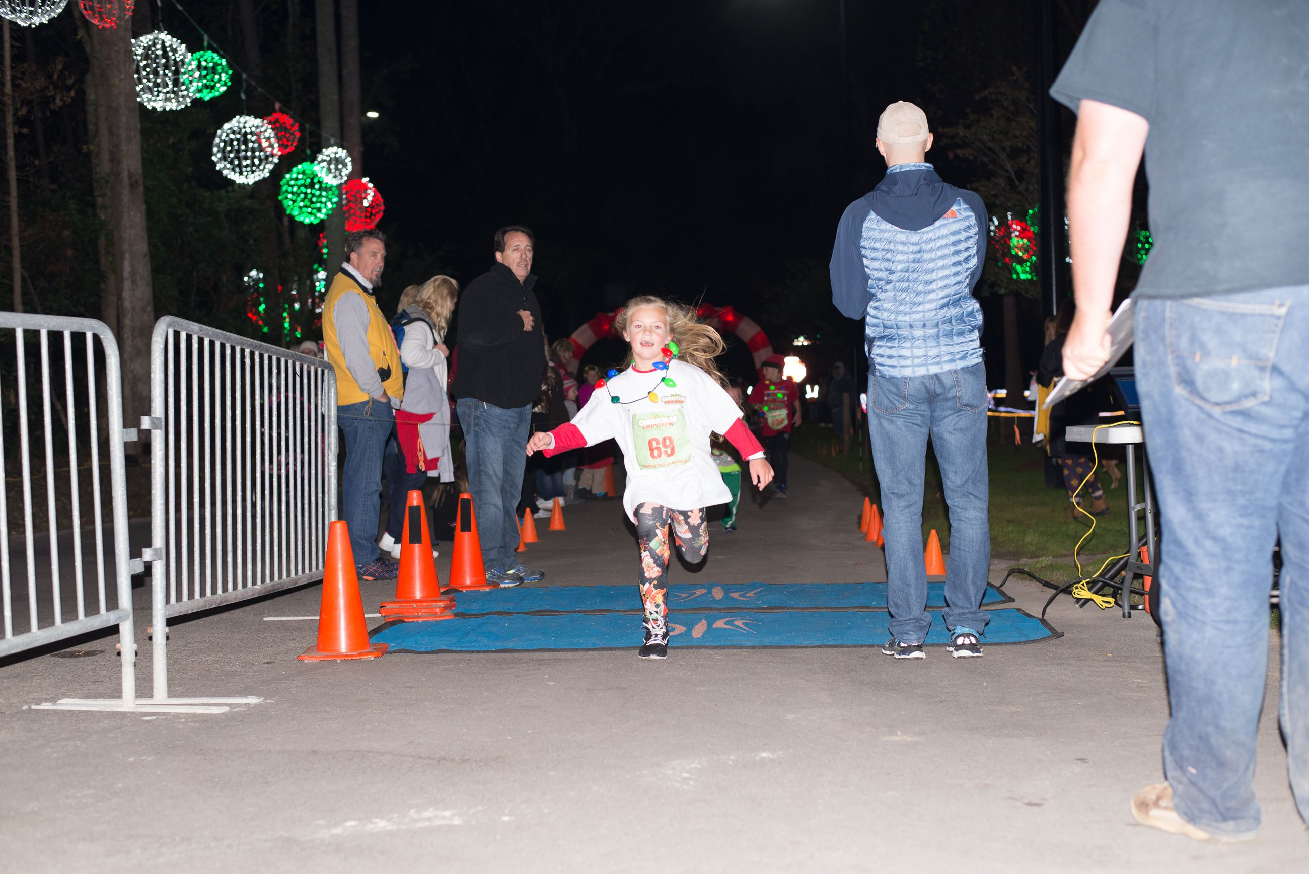 Young Girl Running Across a Finish Line