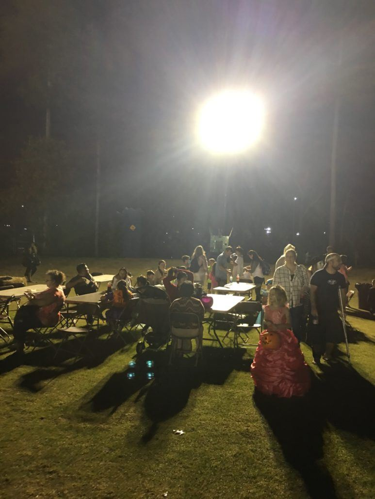 Howl-O-Scream participants sitting at picnic tables at night